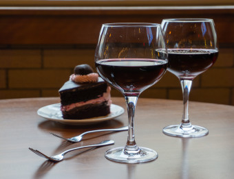 Two glasses of red wine on a table next to a plate of dessert and two forks.