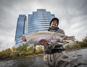 Angler holding a steelhead in the Grand River