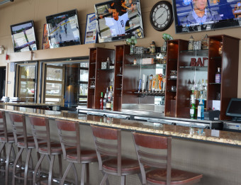 Stools at bar counter facing TVs displaying various sporting events