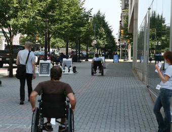 Man on wheelchair travelling on sidewalk in downtown Grand Rapids