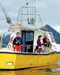 Three people sea fishing from a fishing boat at Kattfjorden in Northern Norway