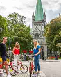 Three people with bikes on a city break in Trondheim, Norway