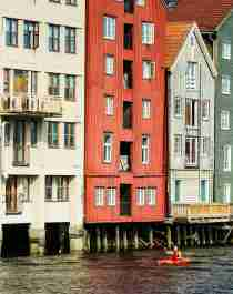 People kayaking on the Nidelven river with old wooden houses in the background. Trondheim, Norway