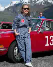 A woman wearing overalls and standing in front of her vintage car, surrounded my other vintage cars and car lovers, Fjord Norway