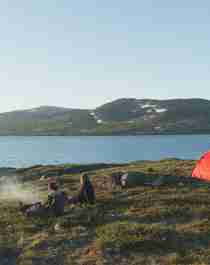Two persons sitting next to their tents whilst enjoying the view