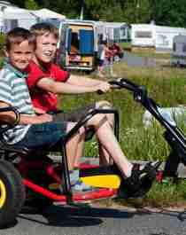 To gutter sitter på en tråbil på Sørlandet feriesenter