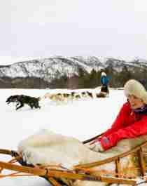 A man and a woman are passengers on a dog sledding trip in Finnmark, Northern Norway