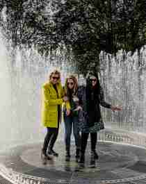 Four laughing women standing in the fountain surrounded by mirrors at Kistefos Museum in Hadeland
