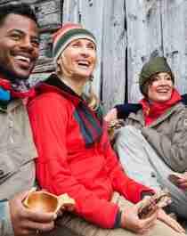 Fire personer sidder udenfor en fjeldhytte i Beitostølen, Norge