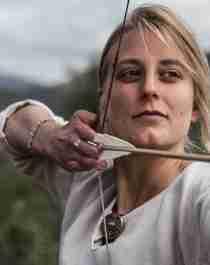 En dame skyter med pil og bue på Lofotr Vikingmuseum på Borg, en av Norges største vikingopplevelser