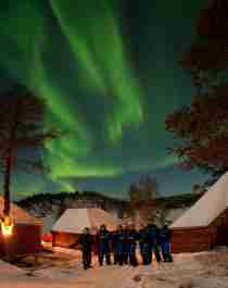 A group of people standing in front of several cabins under the northern lights