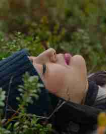 En dame ligger på ryggen og nyter stillheten i en skog på Østlandet