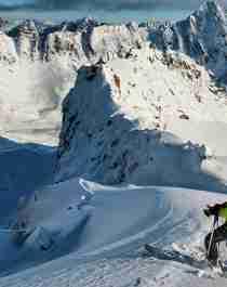 En mann på topptur på ski står klar til å kjøre nedover fjellet