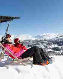 Two people in skiing clothes sit in deck chairs outside Skarsnuten Hotel and enjoy the sunny weather and the wide views of the mountains of Hemsedal, Eastern Norway