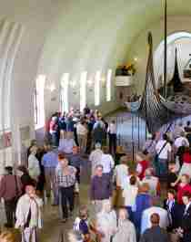 A big crowd observing a viking ship at The Viking Ship Museum in Oslo