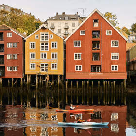 Two people in kayaks along the river in Trondheim