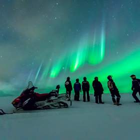 A group of people standing in front of a snowmobile and watching the northen lights in Norway