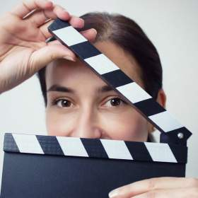 A portrait of Andrea David behind a clapperboard