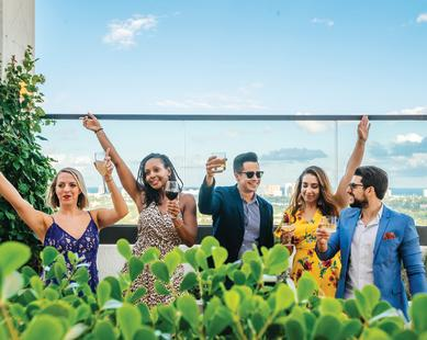 Friends raising glasses to toast from a rooftop bar in Fort Lauderdale