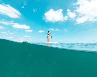 A woman stand-up paddleboarding on the ocean in Fort Lauderdale, FL