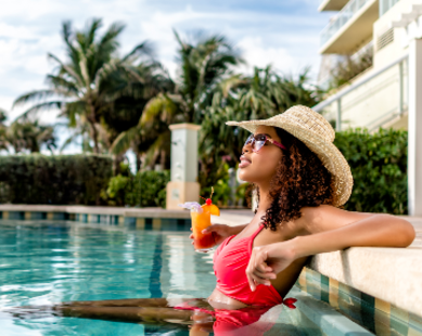 A woman relaxing in the pool with a drink in hand at a Fort Lauderdale resort