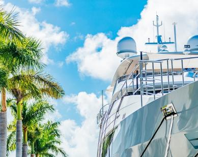 Looking up at a Super Yacht next to palm trees with a blue sky with puffy white clouds