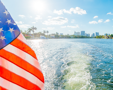 An American flag blowing in the wind on the back of a boat in the water
