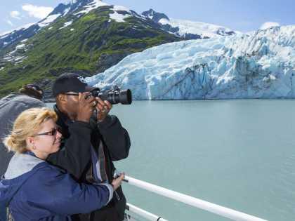 Couple photographs Portage Glacier during glacier cruise