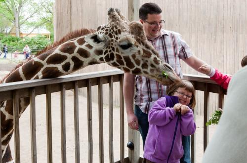 A family has fun feeding a giraffe at the Sedgwick County Zoo