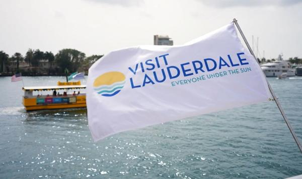 Visit Lauderdale Flag blowing in the wind with the Water Taxi riding behind it.