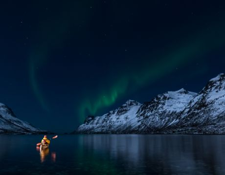A woman paddling under the northern lights in Lofoten