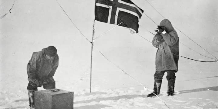Roald Amundsen and Helmer Hanssen next to a Norwegian flag at the South Pole in 1911