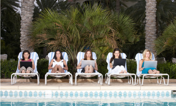 women sitting around pool on laptops