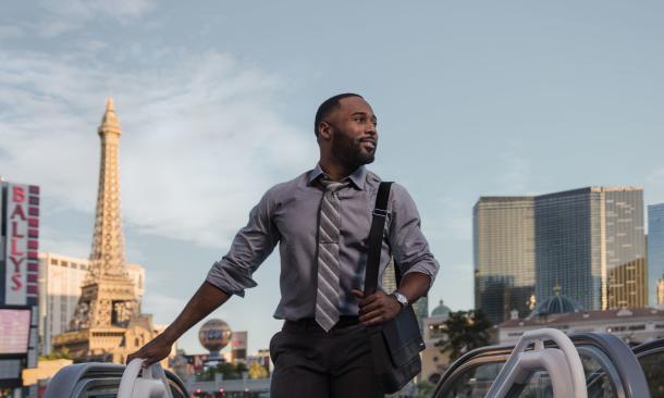 man in business attire at top of escalator in Las Vegas