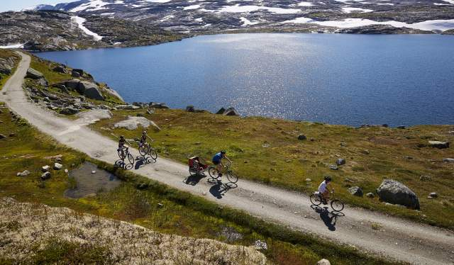 A group biking along a lake at Rallarvegen