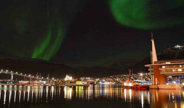 A city view of Tromsø and Scandic Ishavshotel under the northern lights