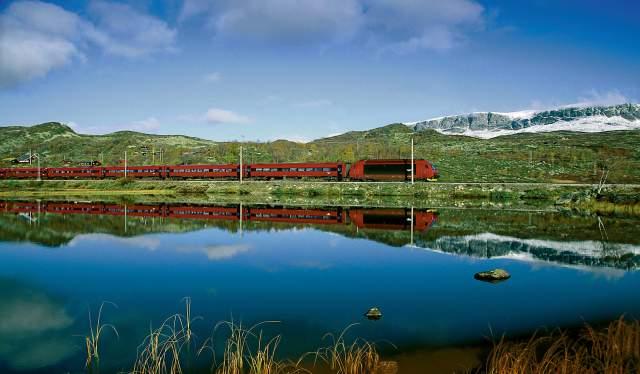 A train passes a lake in Hallingdal on the Bergensbanen Railway