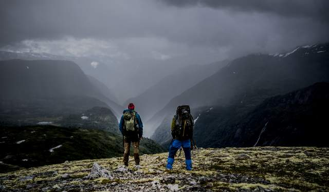 Two people enjoy the view of a rainy Norwegian valley