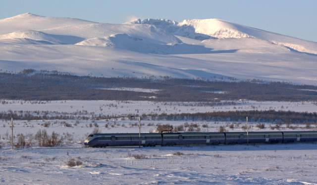 A train riding through the snowy landscape on the Dovre Railway, Eastern Norway
