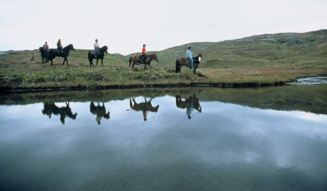 People horse riding next to a lake in Norway