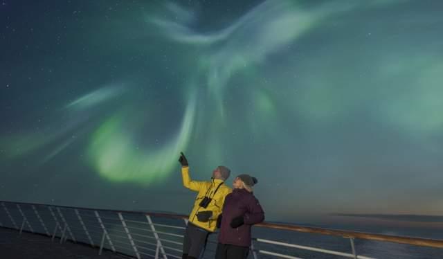 Les aurores boréales sur le pont d'un navire Hurtigruten en Norvèg