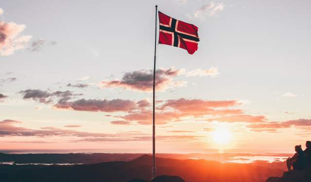 The Norwegian flag and a couple enjoying the sunset on a mountain top