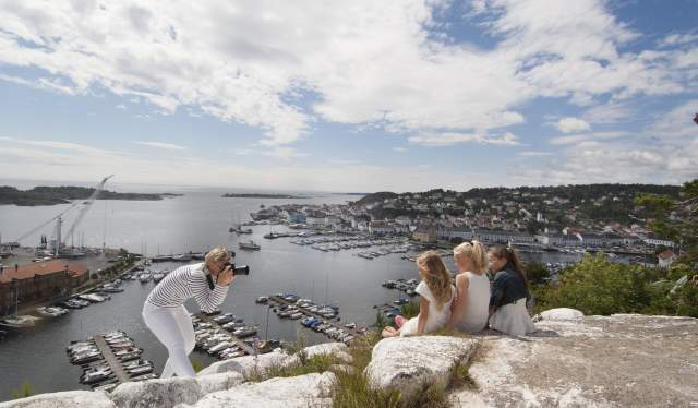 Woman photographing children at Risørflekken viewpoint in Risør