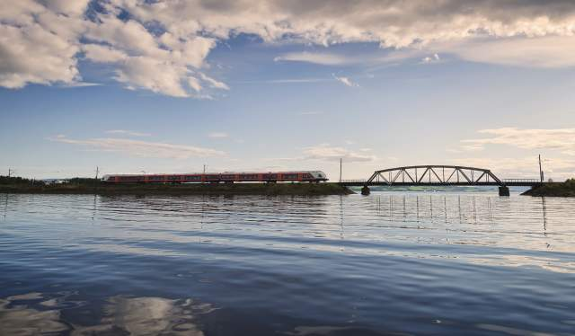 A train on the Sørlandsbanen, crossing a bridge over the water, Southern Norway