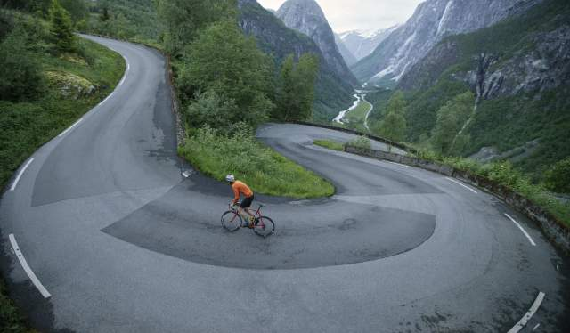A person road cycling up Stalheimskleiva in Norway