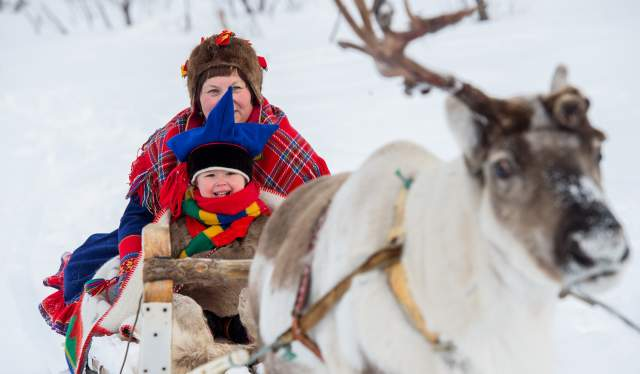 A woman and a little boy riding a reindeer sledge in Finnmark in Northern Norway