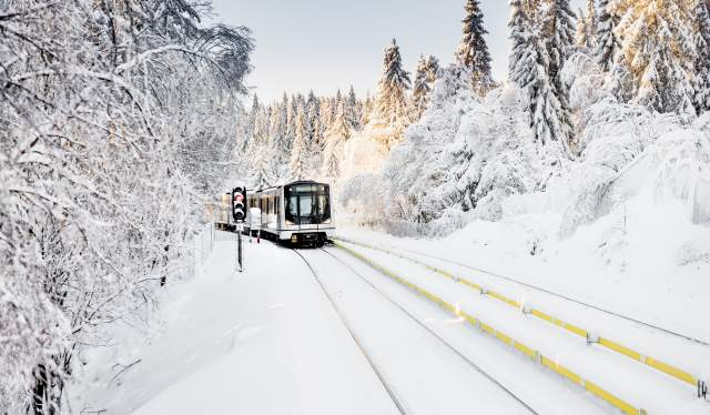 A train riding through a snowy winter landscape near Oslo, Eastern Norway