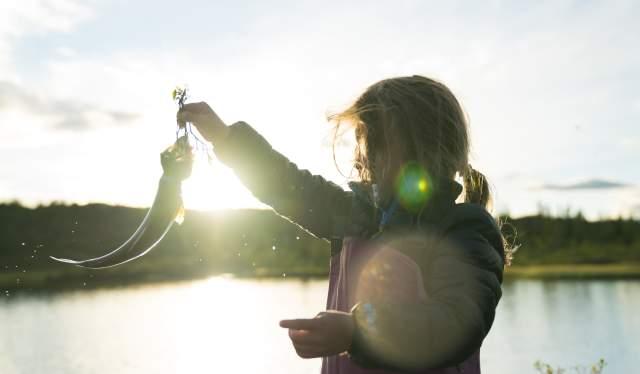 En liten jente holder frem fisken hun har fått på kroken på Blefjell.