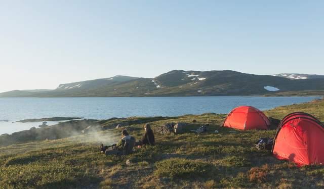 To personer sitter ved siden av teltene sine og nyter utsikten