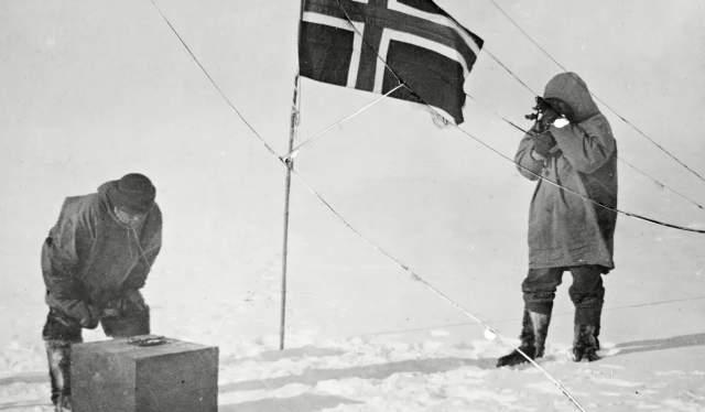 Roald Amundsen og Helmer Hanssen ved siden av et norsk flagg på Sydpolen i 1911